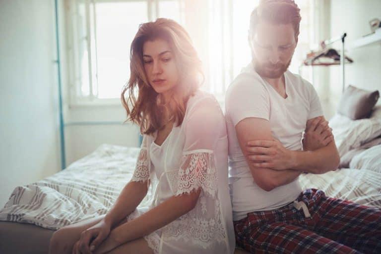 junge Ehepartner sitzen auf dem Bett und sind wütend