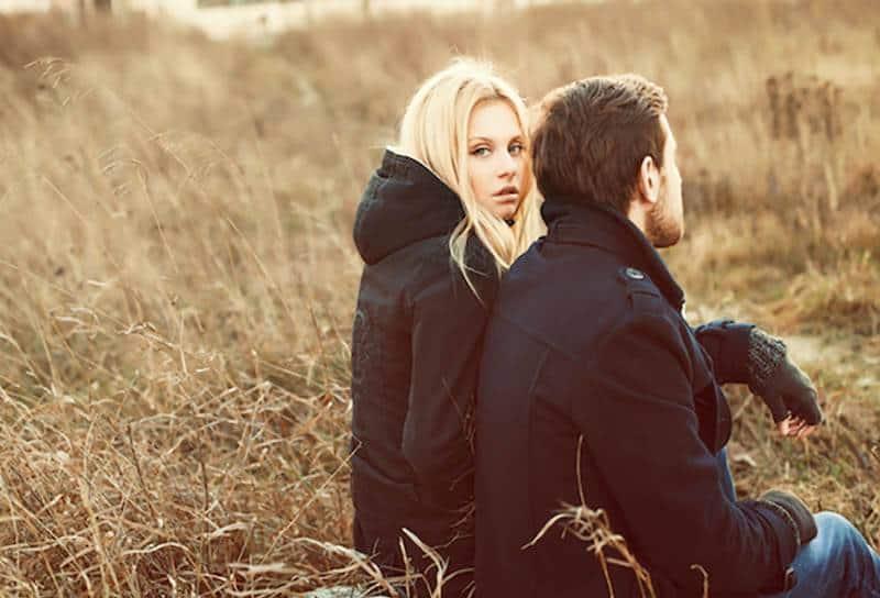 nachdenkliche blonde Frau, die neben Mann sitzt, der schwarze Jacke und Handschuhe draußen trägt
