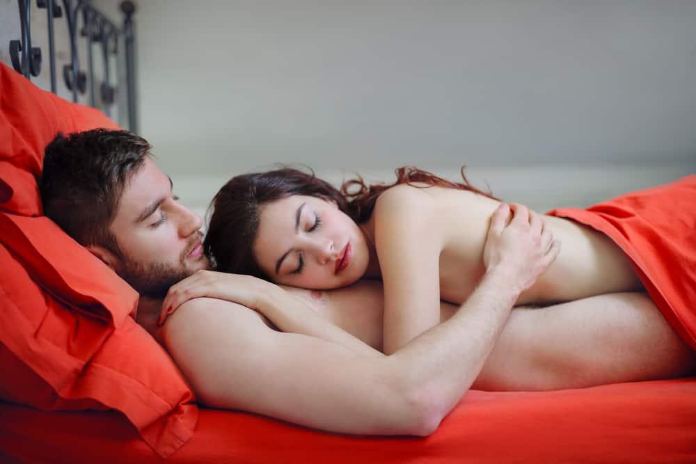 nackte Liebende liegen unter einem roten Laken