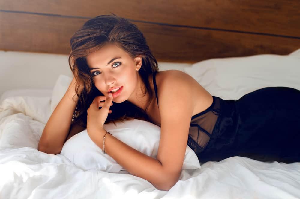 perfekte sexy Brünette auf dem Bett liegen