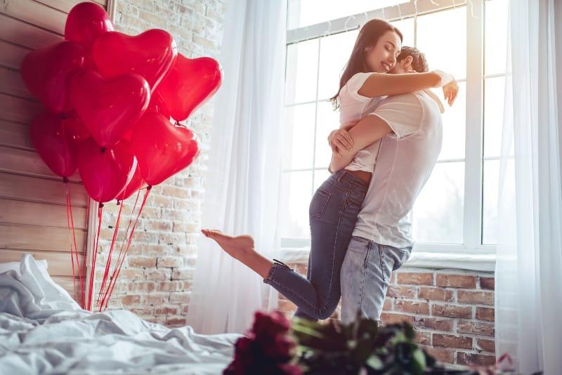 rote herzförmige Luftballons und ein liebevolles Paar in einer starken Umarmung