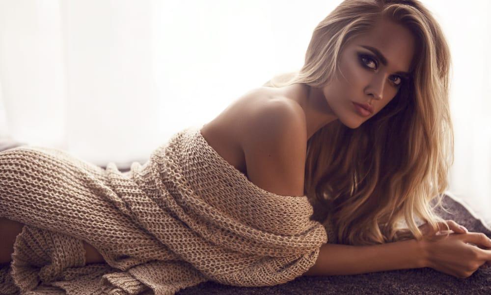 sexy Blondine liegt auf dem Bett