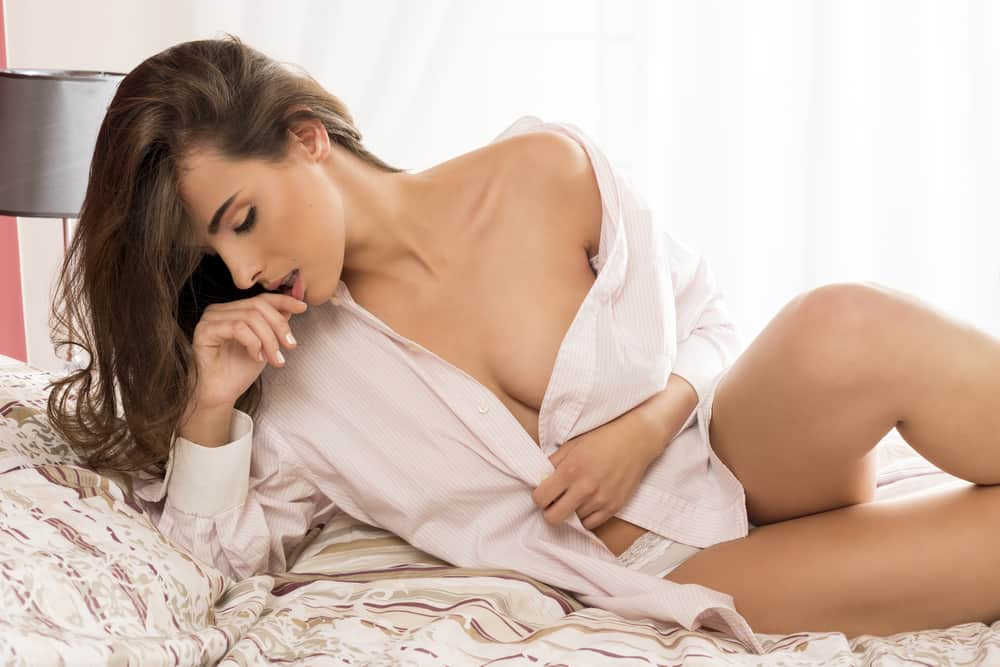 sexy Brünette aufgeknöpftes Hemd im Bett liegend