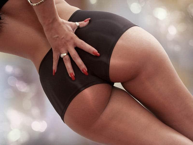 weibliche Hand mit rotem Nagellack auf sexy Arsch