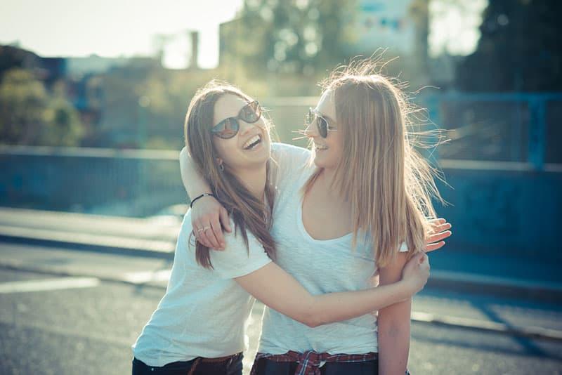 zwei lächelnde Frauen mit Brille umarmen sich