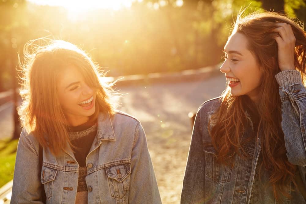 zwei lächelnde Freunde, die durch den Park gehen und reden