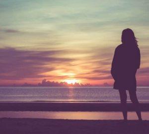ein Mädchen beobachtet den Sonnenuntergang