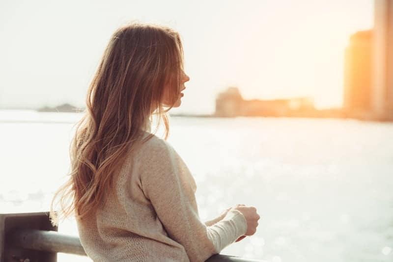 Am Zaun über dem Meer steht eine Blondine in einem grauen Pullover