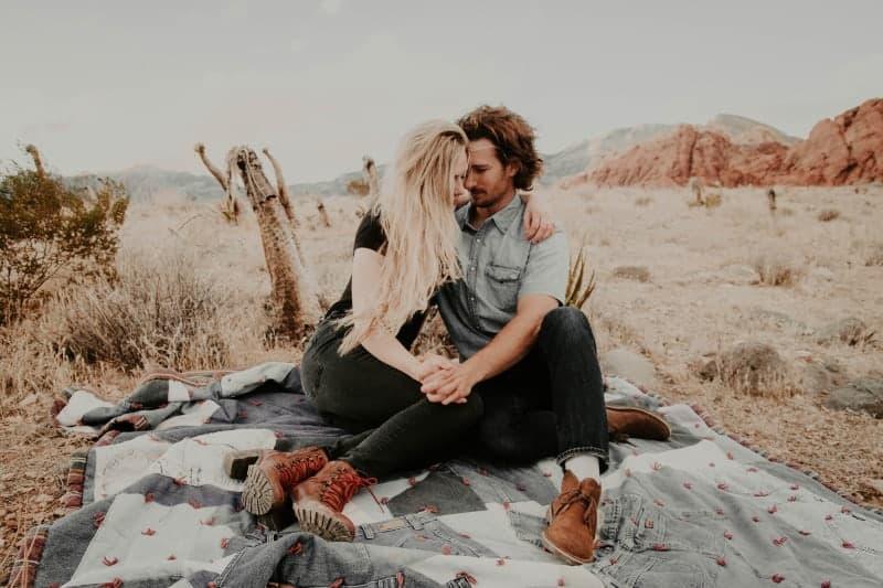 Auf dem Feld auf einer Decke sitzt ein liebevolles Paar in einer Umarmung Händchen haltend