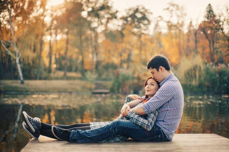 Auf dem Pier des Sees sitzt ein liebevolles Paar in einer Umarmung