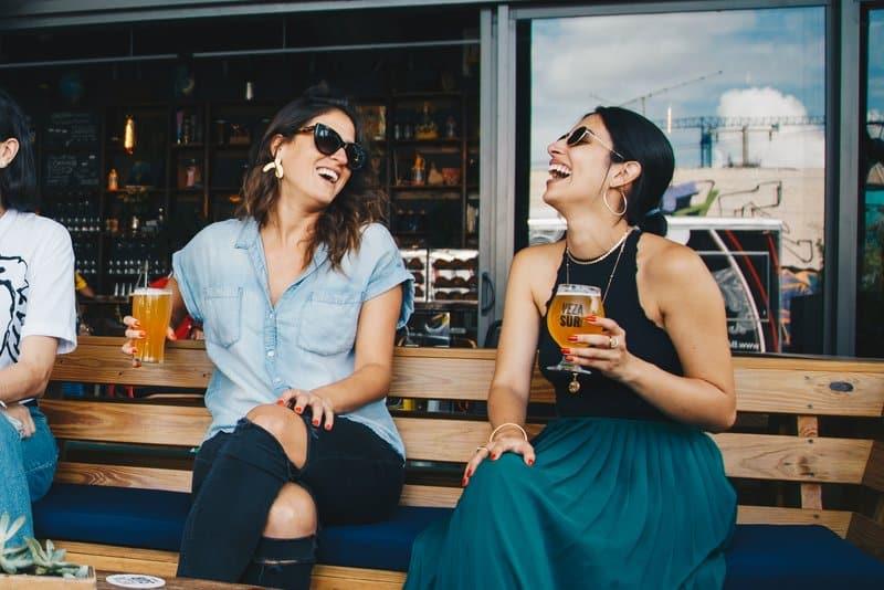 Auf der Terrasse des Cafés sitzen auf einer Holzbank zwei lächelnde Frauen, die Bier trinken