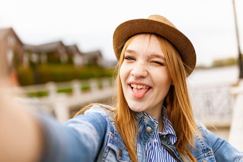 Das Mädchen mit dem Hut macht ein lustiges Selfie
