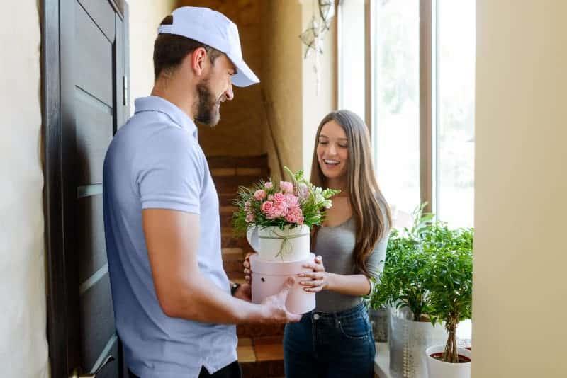 Der Lieferbote übergibt einem lächelnden Mädchen einen Geschenkstrauß