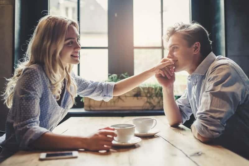 Der Mann am Tisch sitzt mit seiner lächelnden Freundin und küsst ihre Hand