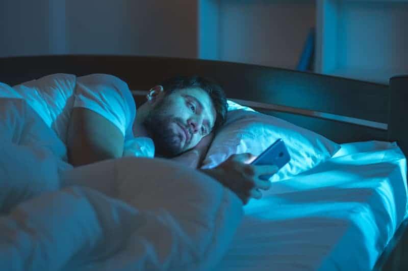 Der Mann liegt im Schlafzimmer und benutzt ein Handy