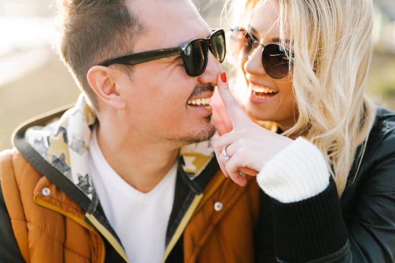 Die glückliche Blondine hält einen Finger an die Nase ihres lächelnden Mannes