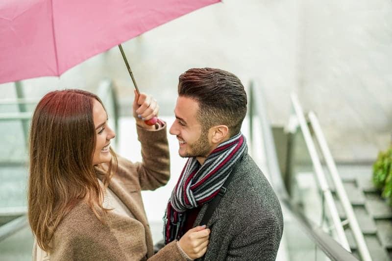 Draußen unter einem Regenschirm stehen ein lächelnder Mann und eine lächelnde Frau
