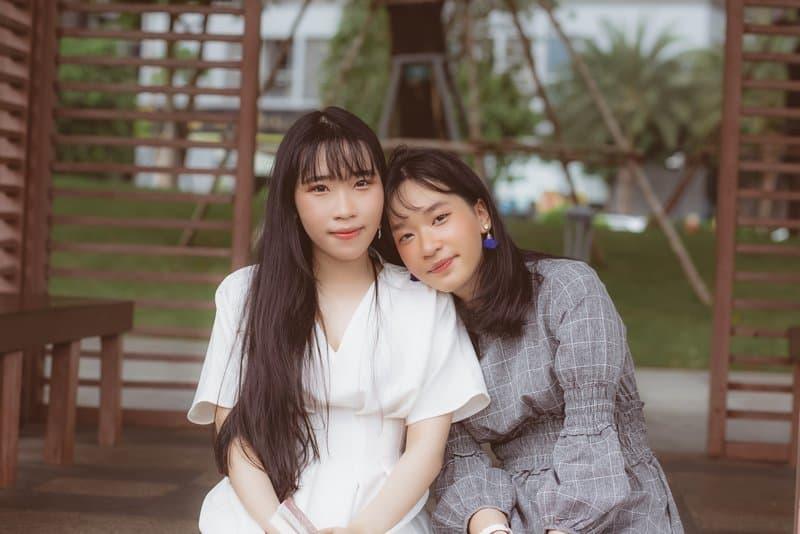 Draußen sitzen zwei asiatische Frauen nebeneinander