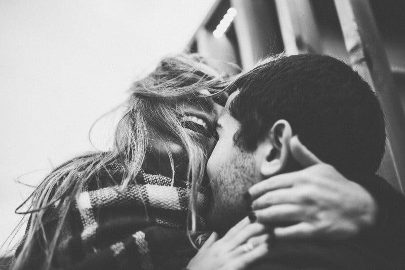 Draußen umarmt eine lächelnde Frau ihren Mann