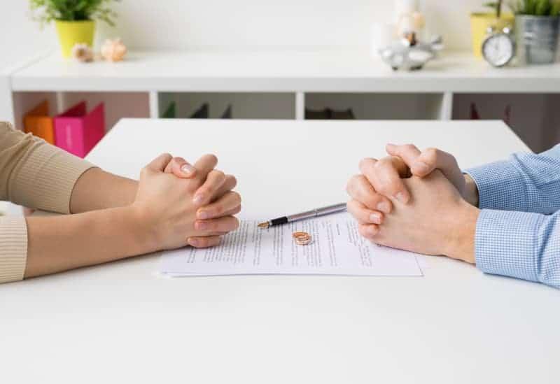 Ehevertrag, Ringe und Hände eines Mannes und einer Frau auf einem weißen Tisch