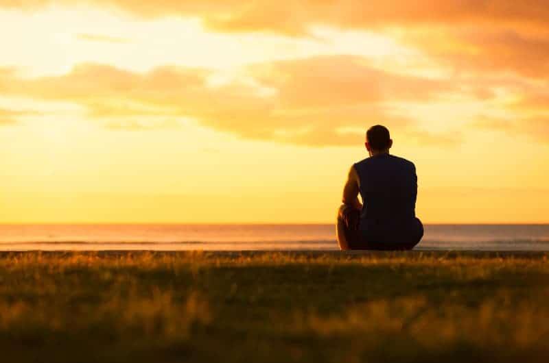 Ein Mann in einem ärmellosen T-Shirt sitzt im Gras und beobachtet den Sonnenuntergang über dem Meer
