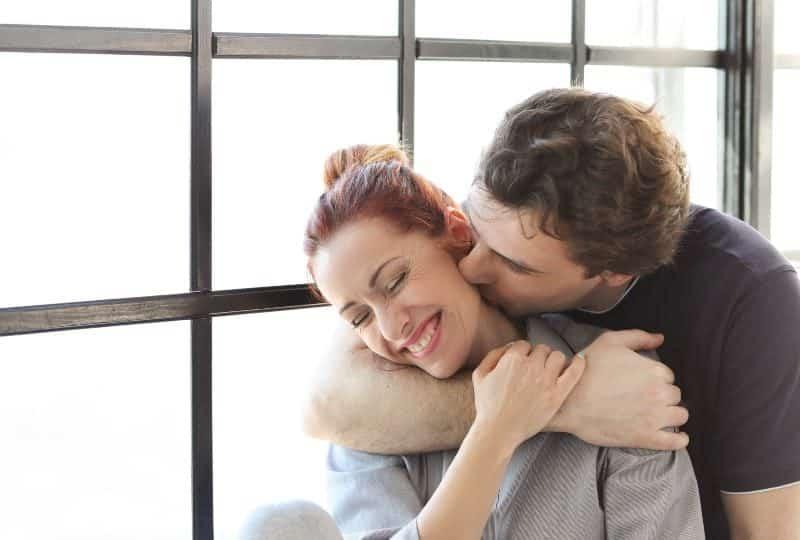 Ein Mann küsst den Hals einer lächelnden glücklichen Frau