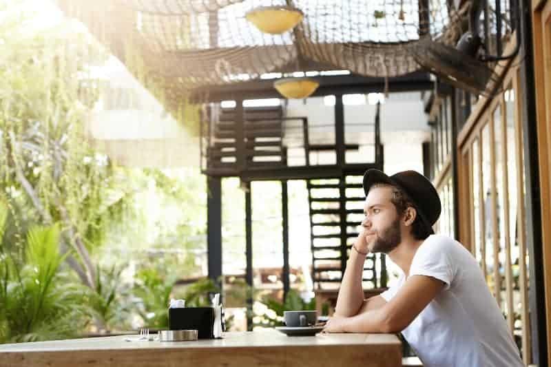 Ein Mann mit Hut auf der Terrasse eines Cafés trinkt Kaffee
