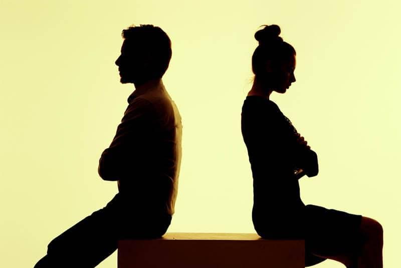 Ein Mann und eine Frau sitzen sich auf einem Würfel gegenüber