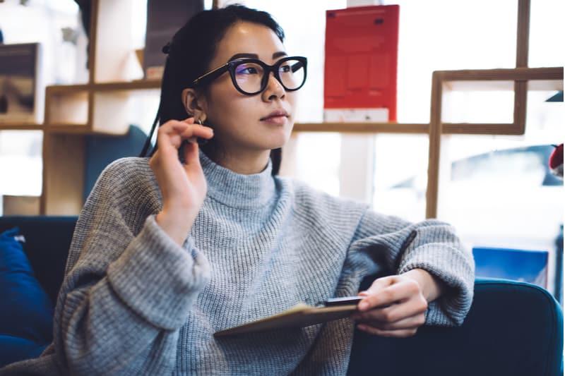 Ein asiatisches Mädchen mit Windeln sitzt und denkt nach
