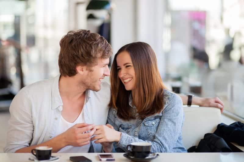 Ein glückliches Liebespaar sitzt Händchen haltend in einem Café
