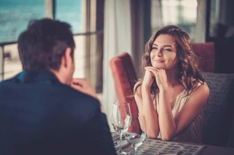 Ein lächelndes Paar sitzt in einem Restaurant und schaut sich verliebt an
