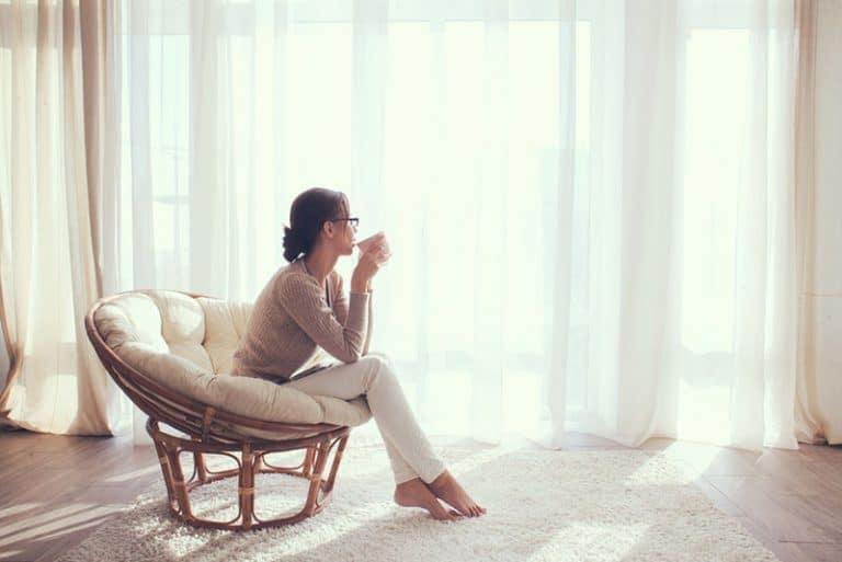 Ein nachdenkliches Mädchen schaut aus dem Fenster und trinkt Kaffee