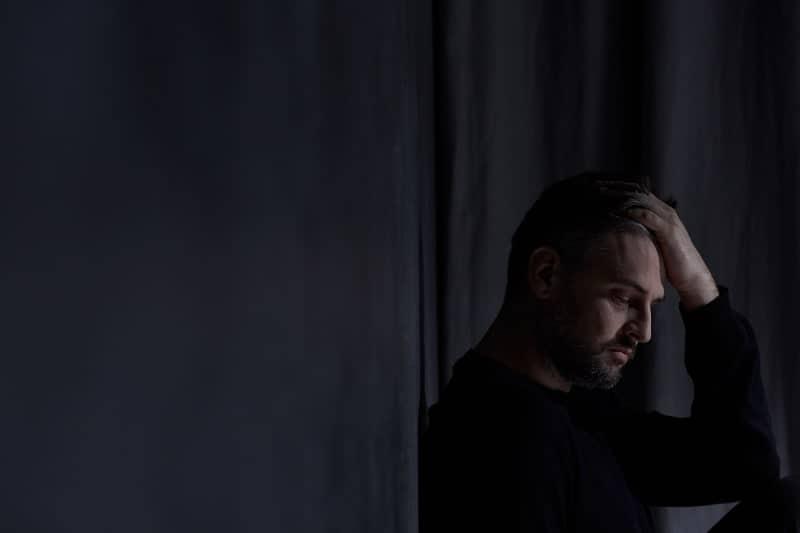 Ein trauriger Mann sitzt im Dunkeln und lehnt sich an die Wand