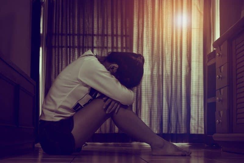 Ein trauriges Mädchen sitzt auf den Fliesen in der Küche und weint