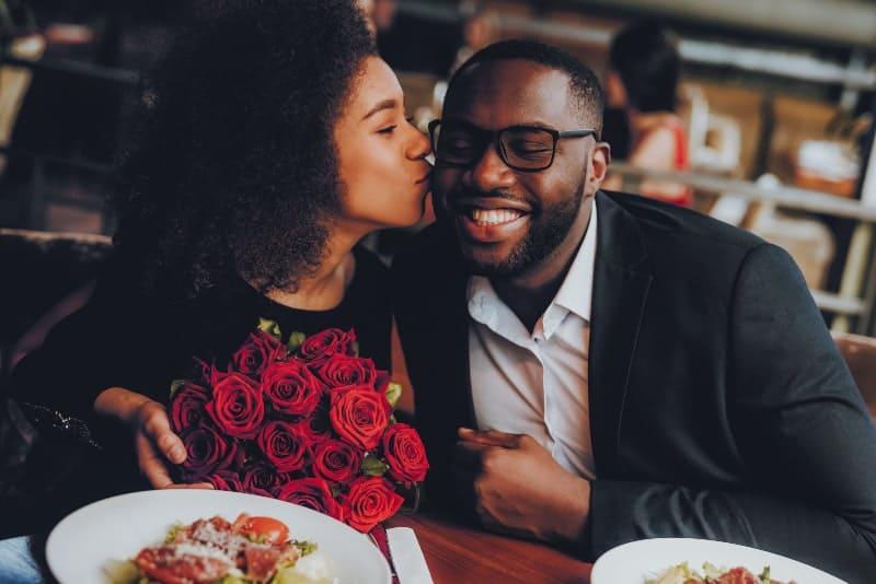 Eine Frau mit einem Rosenstrauß in der Hand küsst einen lächelnden Mann