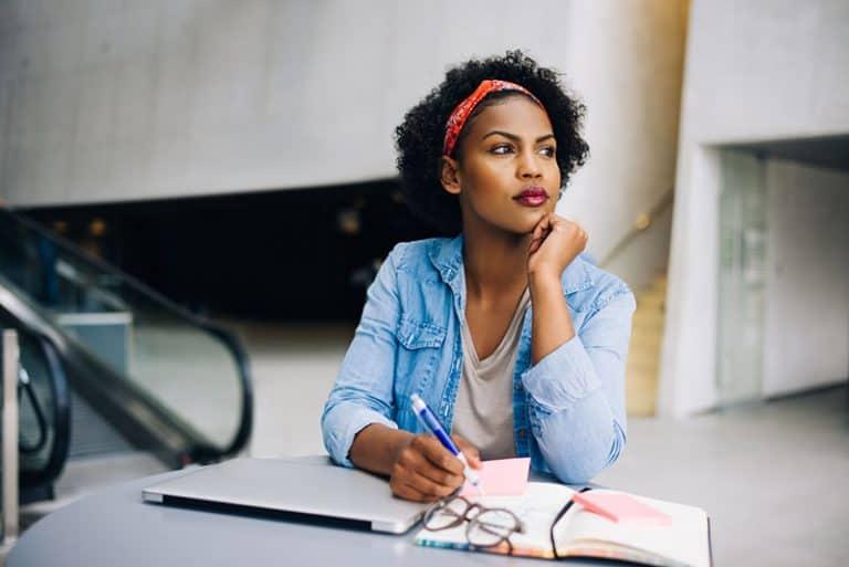 Eine besorgte junge schwarze Frau schreibt ein Tagebuch
