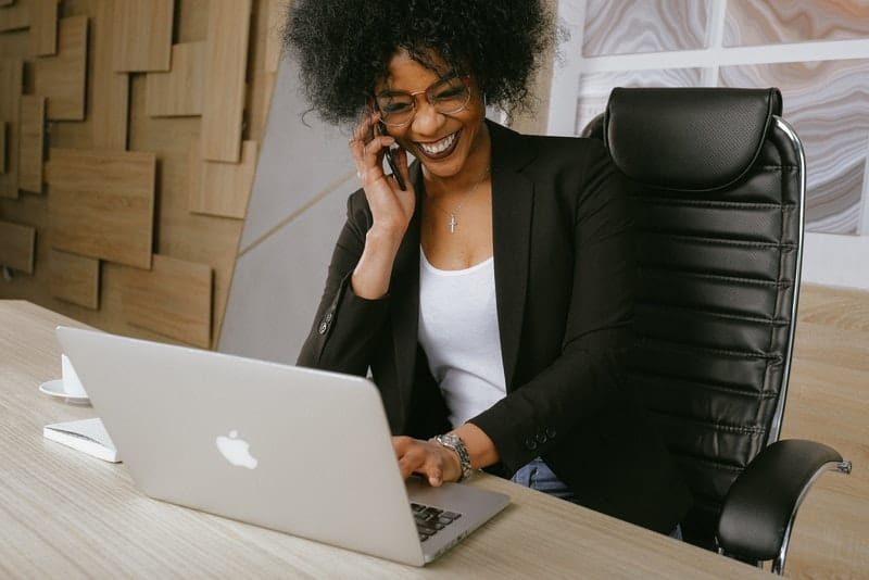Eine lächelnde schwarze Frau sitzt im Büro und spricht auf ihrem Handy