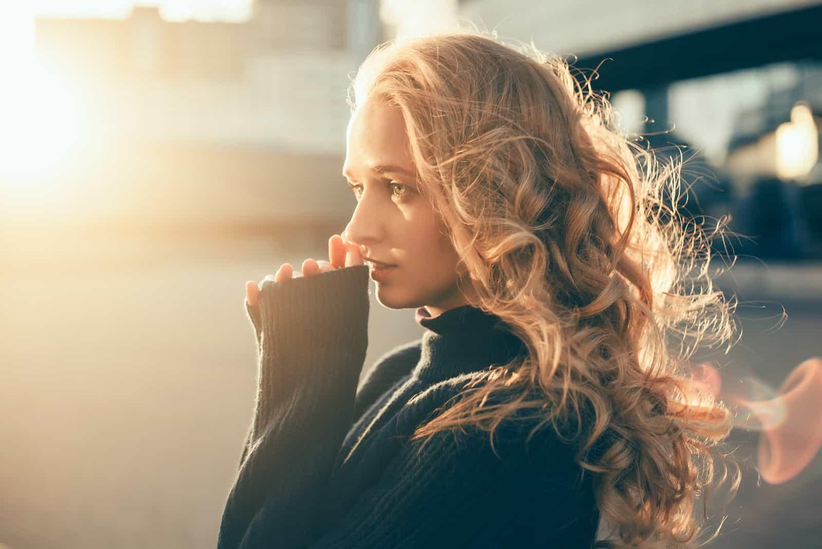 Eine schöne Blondine in einem schwarzen Pullover steht draußen und denkt nach