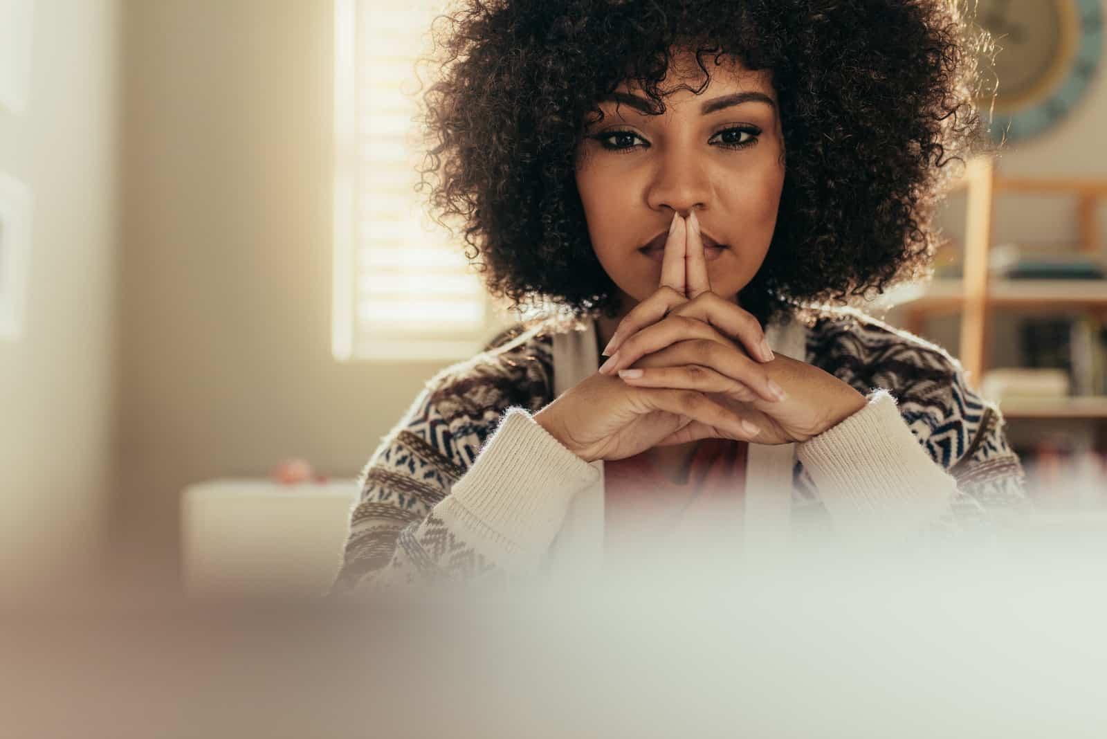 Eine schöne schwarze Frau sitzt an ihrem Schreibtisch und denkt nach