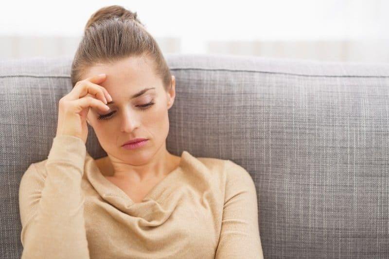 Eine traurige Frau sitzt auf der Couch und hält ihren Kopf