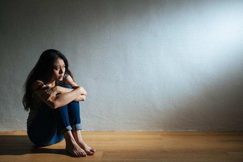 Eine traurige und verängstigte Chinesin sitzt auf dem Boden im Raum