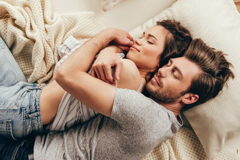 Ein liebendes Paar, das im Bett lag, umarmte sich