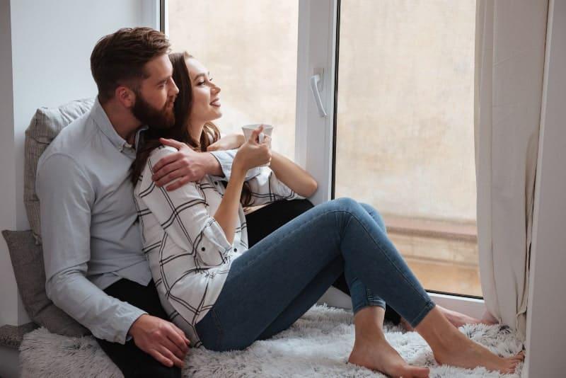 Im Haus am Fenster sitzen zwei verliebte junge Menschen in den Armen