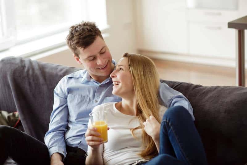 Junger Mann und Frau, die den Orangensaft entspannen und trinken
