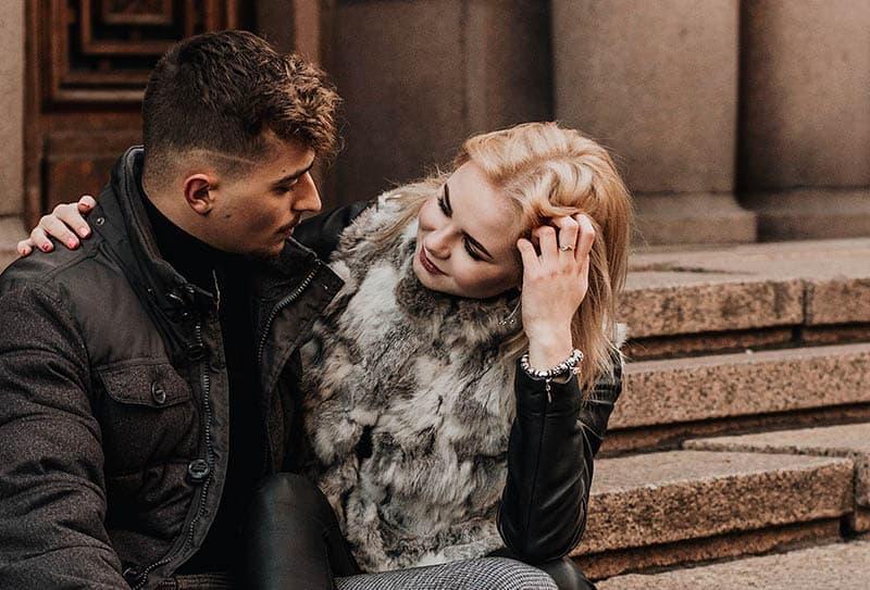Mann und Frau schauen sich an, während sie draußen sitzen