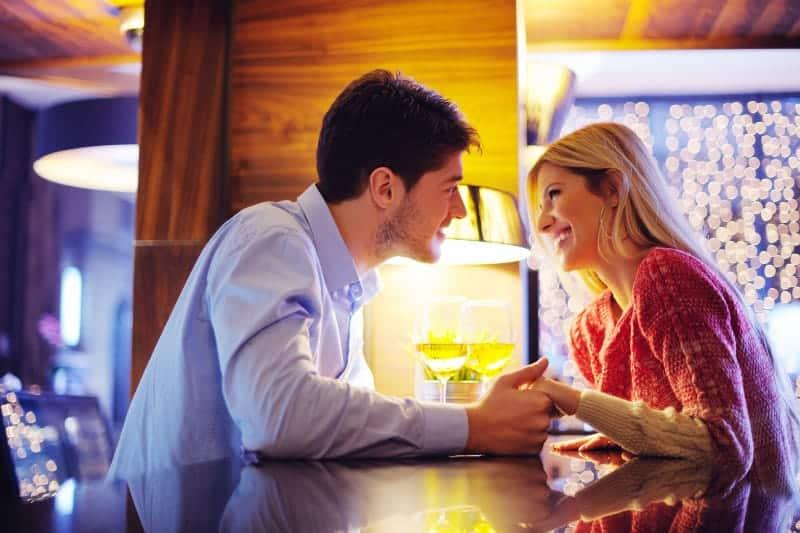 Paar, das sich beim Händchenhalten im Café ansieht