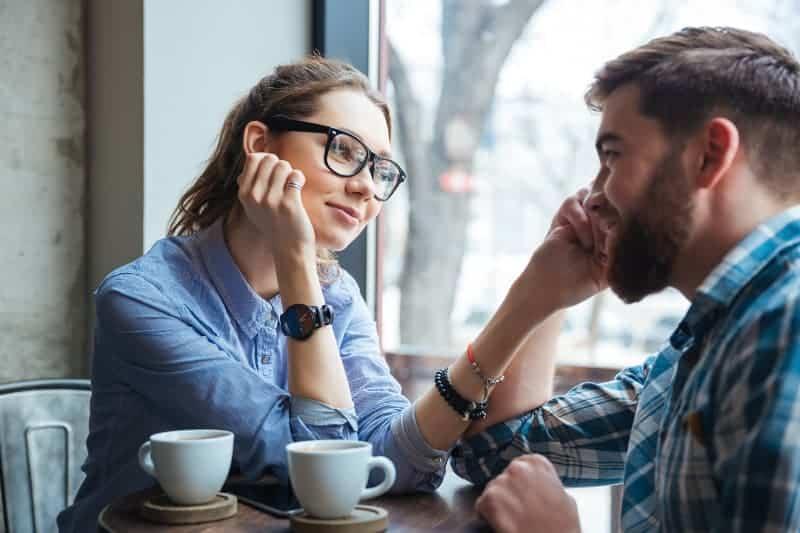 Ein verliebtes Mädchen in Gläsern trinkt Kaffee mit ihrem Freund
