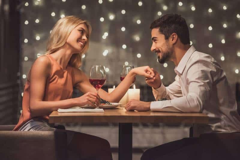 Schönes junges Paar schaut sich an und lächelt während ihres Dates in einem Restaurant,