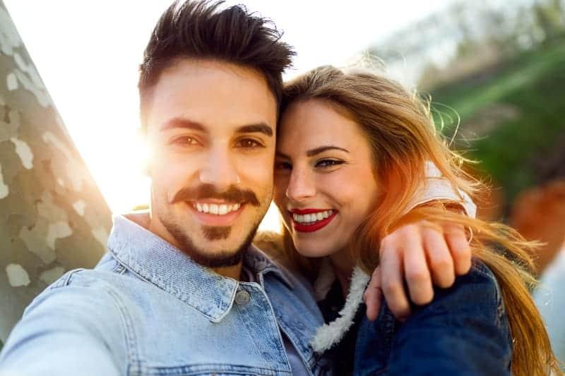 Umarmen eines lächelnden Liebespaares draußen, das ein Selfie-Foto macht