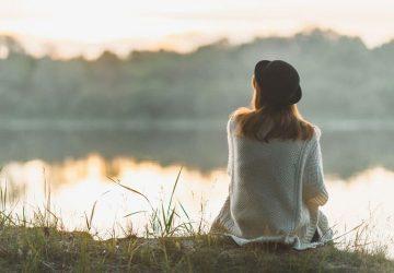 Die Frau sitzt alleine am See